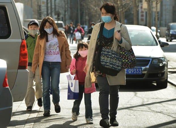 Família chinesa usa máscaras para se proteger da poluição em Pequim (Foto: Mark Ralston/AFP)